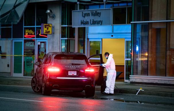 Un policía forense recoge evidencias en la puerta de la biblioteca donde se han producido los apuñalamientos.
