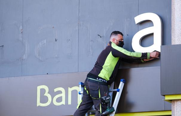 Los operarios desmontan el rótulo de Bankia de la sede principal del banco en Logroño.
