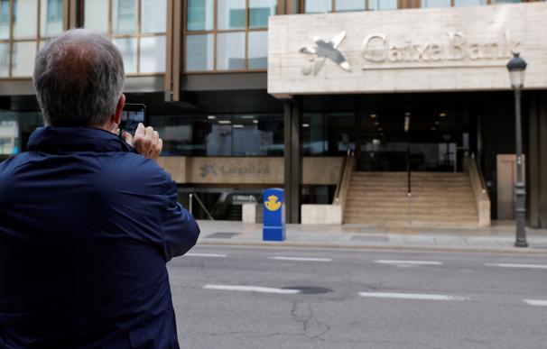 Un hombre toma este domingo una foto del logo de Caixabank que desde ayer sustituye al de Bankia, tras la fusión de ambos bancos, en lo que era la sede social de esta última entidad en Valencia.