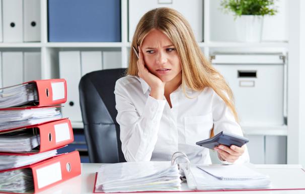 Una mujer preocupada calculando la declaración de la Renta.