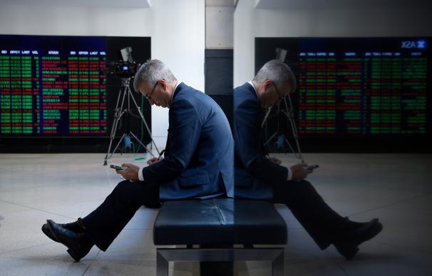 Un operador de bolsa consulta las cotizaciones en su móvil.