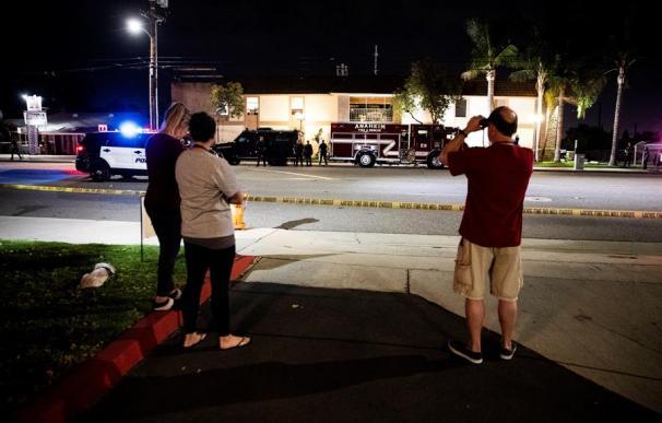 Varias personas observan tras el cordón policial después de que al menos cuatro personas, incluido un menor de edad, murieran este miércoles