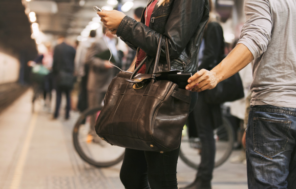 Carterista robando el monedero del bolso de una mujer en el metro.