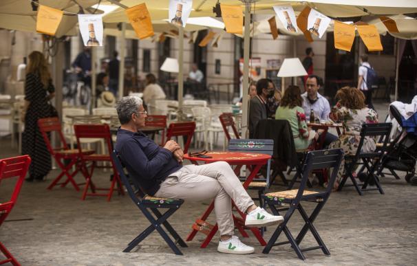 Una persona en un bar decorado con los farolillos tradicionales de la Feria de Abril, suspendida por segundo año consecutivo debido a la pandemia provocada por el coronavirus, Covid-19. En Sevilla (Andalucía, España), a 20 de abril de 2021. María José López / Europa Press 20/4/2021