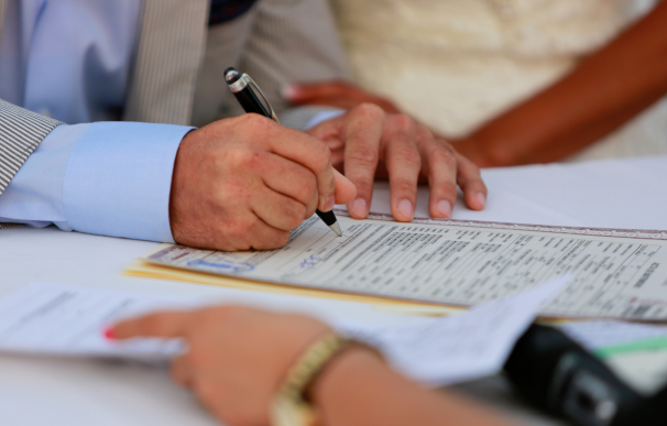 Matrimonio firmando el registro del Libro de Familia.