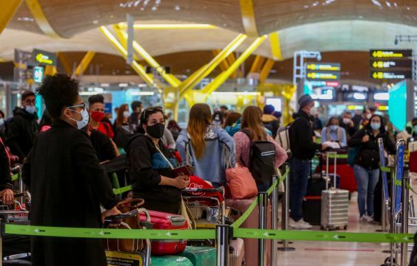 Filas de pasajeros esperan para dejar su maleta antes de embarcar