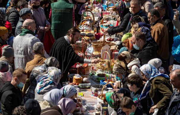 Un sacedote ortodoxo bendice pasteles y huevos de Pascua en un mercadillo en Moscú.