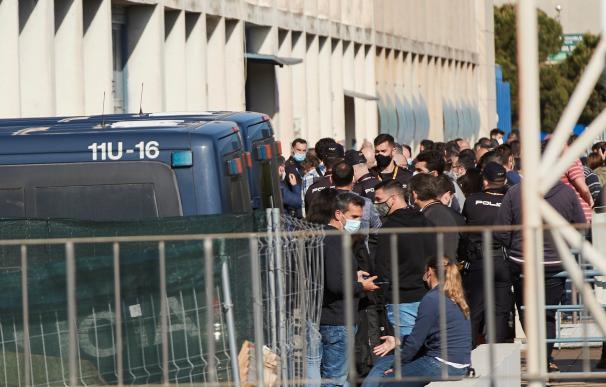 Agentes de la Guardia Civil y de la Policía Nacional en Cataluña guardan cola en las puertas de la comisaría de la Policía Nacional en la Zona Franca de Barcelona donde este lunes ha arrancado la vacunación
