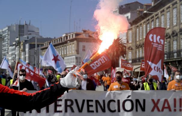 Decenas de personas con banderas de sindicatos y humo durante una manifestación