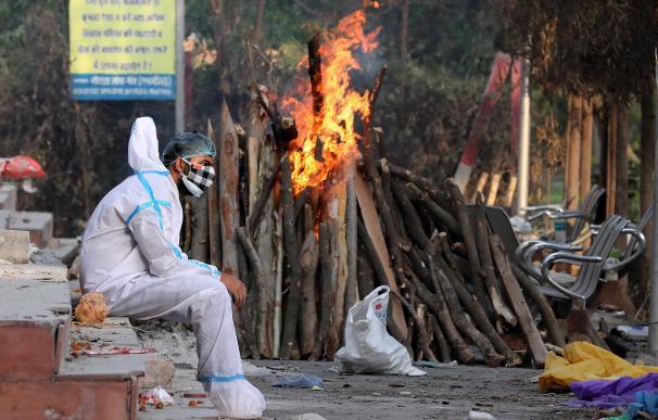 Un hombre ataviado con un traje aislante permanece sentado tras realizar rituales funerarios a sus familiares difuntos