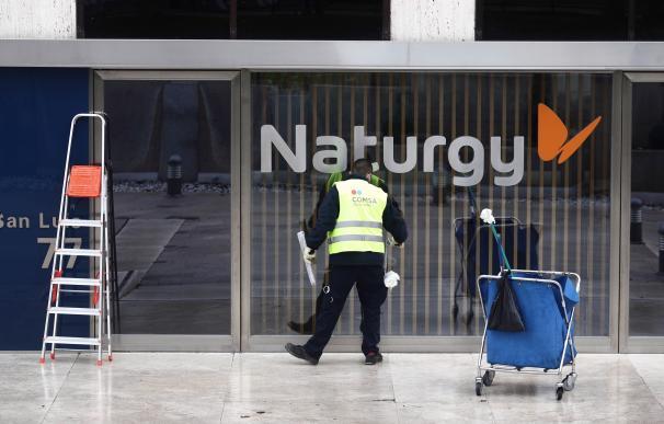 Un operario limpia la cristalera de la sede de Naturgy