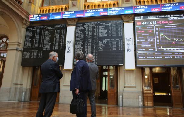 Tres hombres observan valores económicos en el Palacio de la Bolsa, en Madrid.