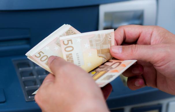 Persona sacando billetes de 50 euros del cajero.