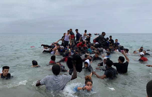 Un grupo de personas se hacen con una embarcación de las autoridades marroquíes en la playa de la localidad de Fnideq (Castillejos) para cruzar los espigones de Ceuta.