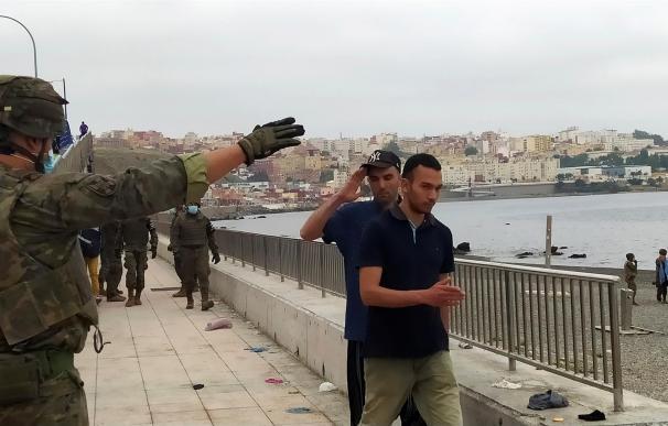 Un miembro del Ejército de Tierra da instrucciones a un grupo de inmigrantes en uno de los espigones fronterizos de Ceuta
