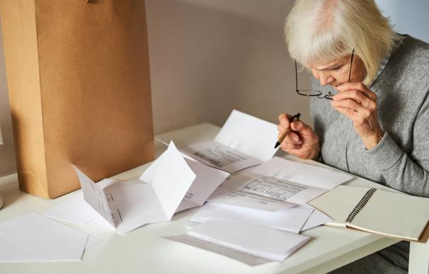 Una mujer revisando sus facturas de la luz.