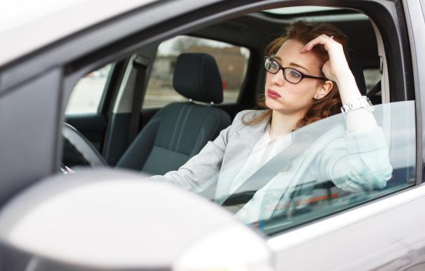 Una mujer llegando tarde al trabajo por el tráfico.