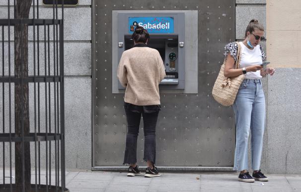 Dos mujeres en un cajero de una sucursal de banco Sabadell.