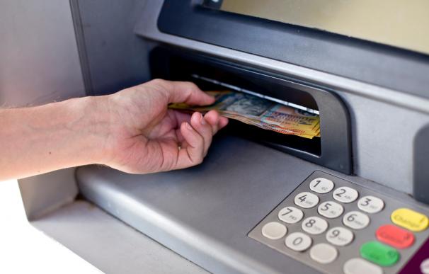 Sacar dinero efectivo en un cajero del banco.